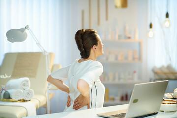 tired woman worker having back pain in modern beauty salon - fototapety na wymiar