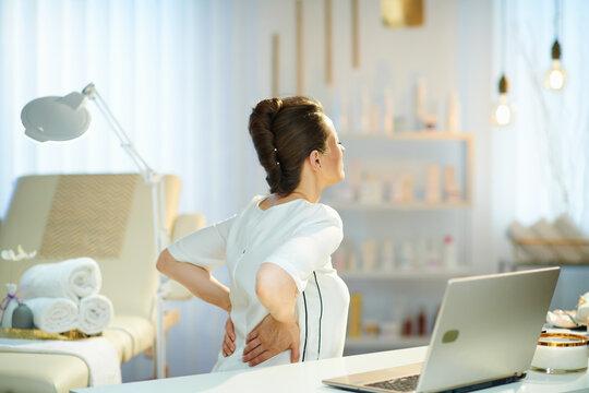 tired woman worker having back pain in modern beauty salon