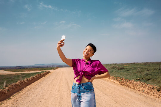 Amused young woman takes a selfie with her tongue out