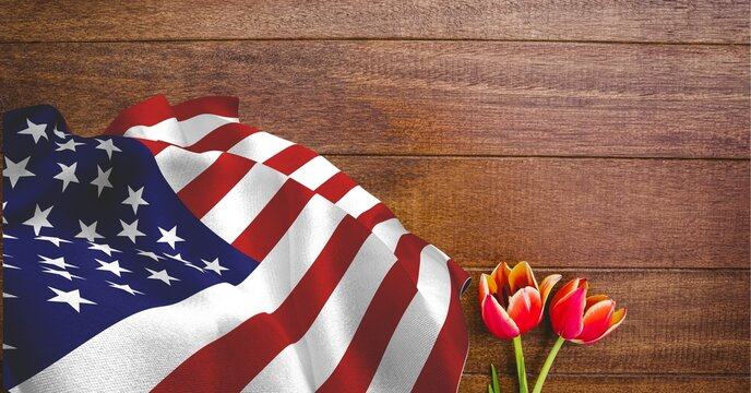 American flag and red tulip flowers on wooden background