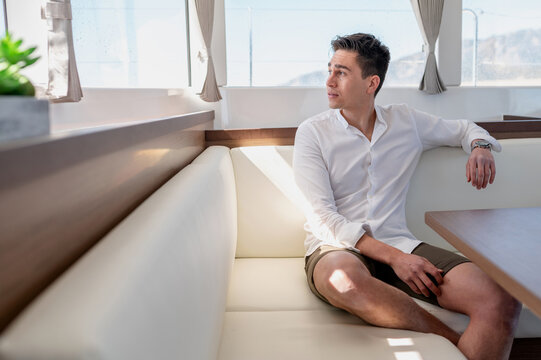 Content man sitting in cabin of modern yacht