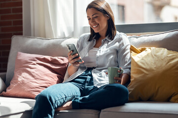 Fototapeta Pretty young smiling woman using mobile phone sitting on a couch at home. obraz