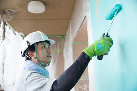 真剣に仕事する若い日本人の塗装業、仕事中の横顔