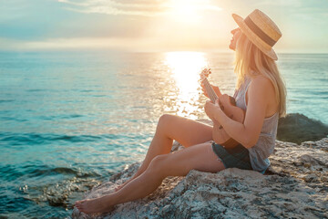 Fototapeta Summer Vacation. Smelling caucasian women relaxing and playing on ukulele on beach, so happy and luxury in holiday summer, outdoors sunset sky background. Travel and lifestyle Concept.  obraz