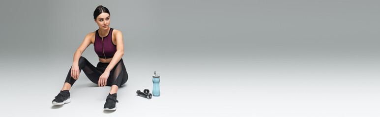 Fototapeta sportive woman looking away while sitting near sports bottle and dumbbells on grey background, banner. obraz