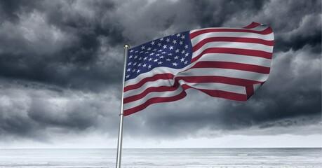 Samenstelling van wuivende Amerikaanse vlag tegen stormachtige lucht en aan zee