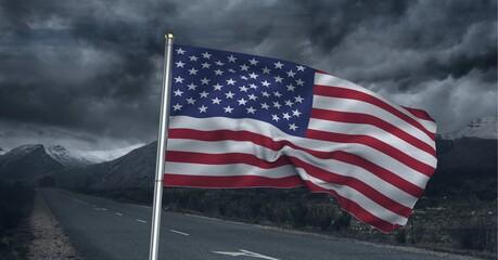 Samenstelling van wuivende Amerikaanse vlag tegen stormachtige lucht en plattelandsweg