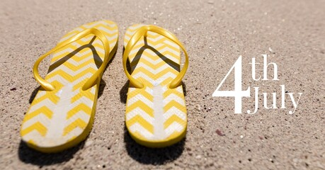 Samenstelling van gelukkige 4 juli-tekst met slippers op zand