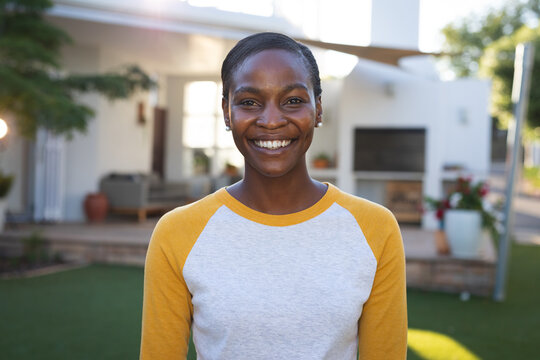 Portrait of happy african american woman standing in garden smiling to camera, house in background