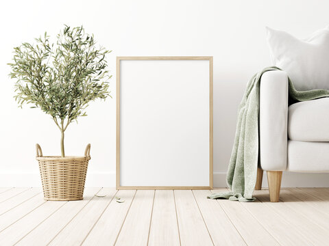 Vertical poster mockup with wooden frame standing on floor in traditional living room interior with sofa and olive tree in wicker basket on empty wall background. 3D rendering, illustration