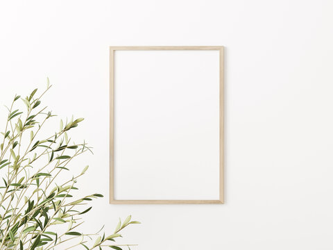 Simple vertical wooden frame mockup with green olive tree branches on empty white wall background. A4, A3, A size, 3D rendering, illustration