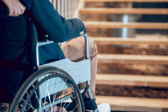 Man in wheelchair stopped near stairs