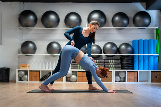 Woman practicing yoga with instructor