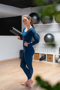 Positive young woman with yoga mat in studio