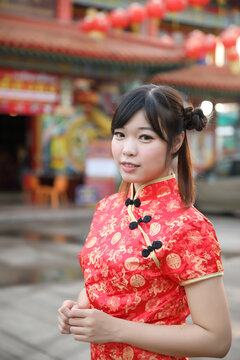 beauty woman wear red cheongsam looking and smile in chinese new year