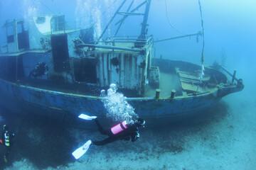 Scuba Divers Exploring underwater ship wreck. Diver discovering the shipwreck sunken at deep sea bottom