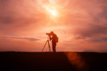 silhouette of Travel photographer standing with a camera mounted on a tripod