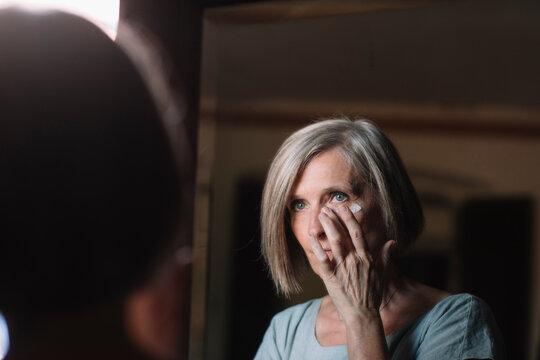 Short haired woman looking in mirror while applying face cream at home