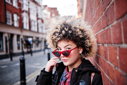 Curly haired woman wearing sunglasses by wall at Chinatown during vacations
