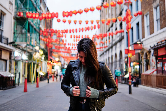Woman wearing leather jacket looking down while standing on street in city
