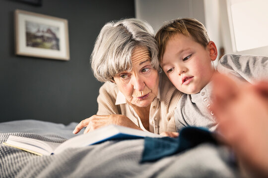 Grandmother reading book by grandson in bedroom at home