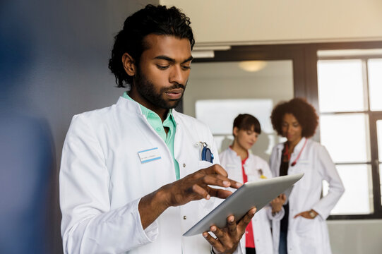 Young male healthcare worker using digital tablet with female colleagues standing in background at hospital