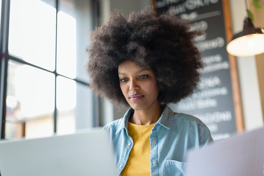 Afro businesswoman looking at laptop in cafe