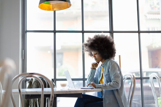 Businesswoman working on laptop while sitting in cafe