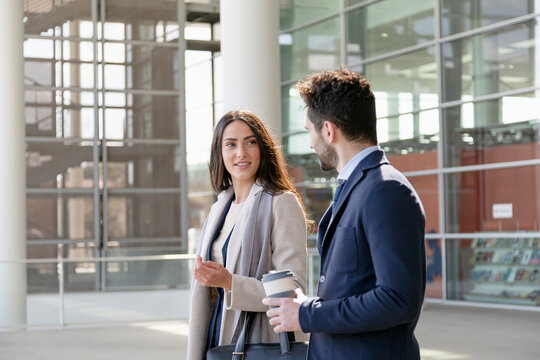 Young businesswoman holding purse while talking with colleague