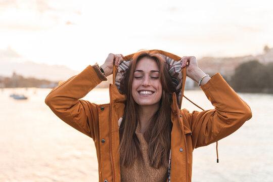 Spain, Cantabria, San Vicente de la Barquera, Smiling young woman enjoying sea coast at sunset