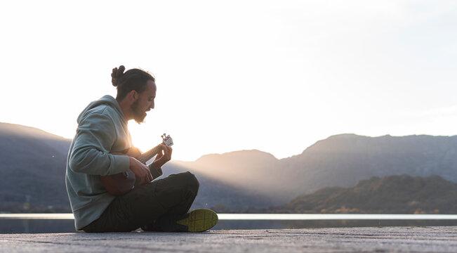 Young man singing while playing ukulele on promenade during sunny day