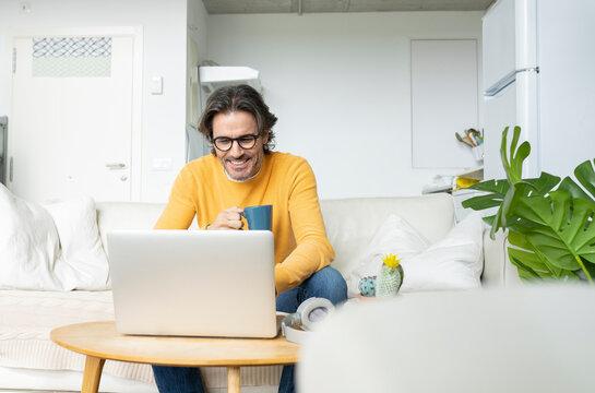 Smiling man holding mug while using laptop at home