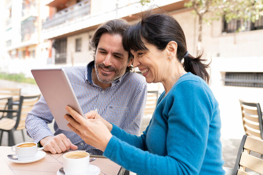 Couple using digital tablet while sitting at terrace