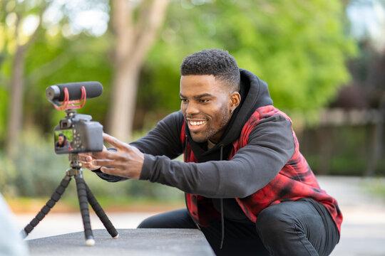 Smiling male vlogger adjusting camera on tripod at public park