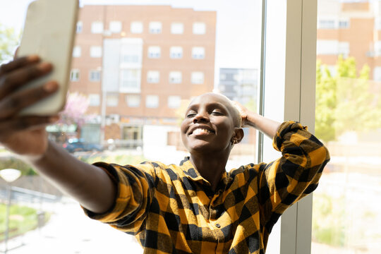 Smiling short haired woman taking selfie by window at home