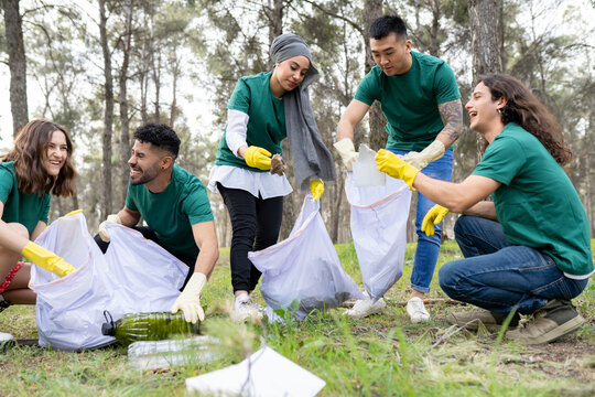 Smiling male and female volunteers collecting plastic in forest