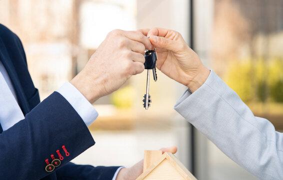 Mature real estate agent giving house keys to female entrepreneur