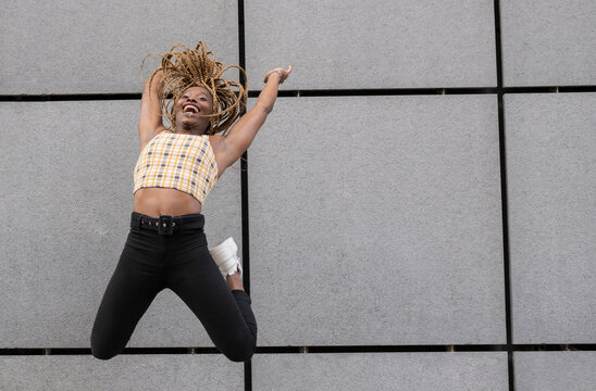 African woman jumping with arms raised by wall