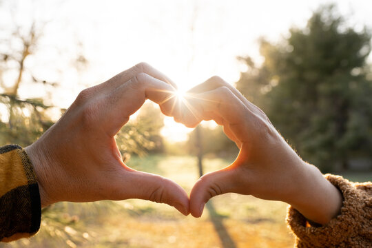 Man and woman's hands making heart shape symbol during sunset