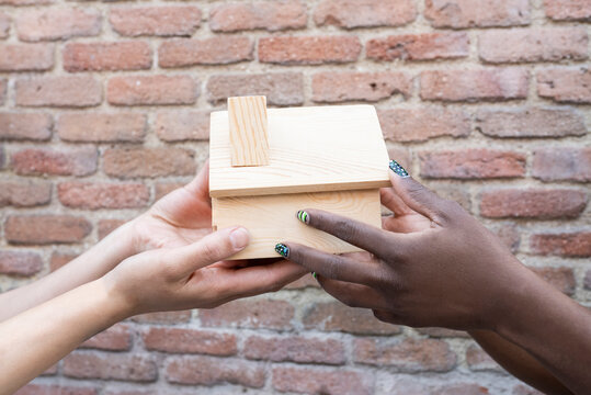 Female friends holding house model by brick wall