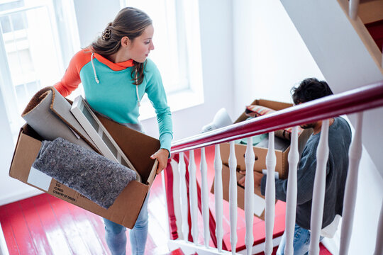 Young couple carrying boxes while moving up on staircase at home