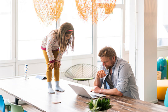 Businessman using laptop by daughter standing on table at home