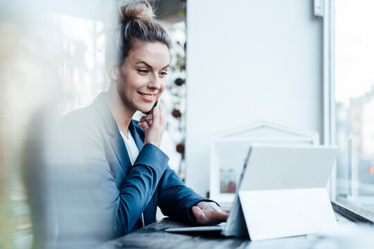 Mid adult female entrepreneur using digital tablet while talking on mobile phone at cafe