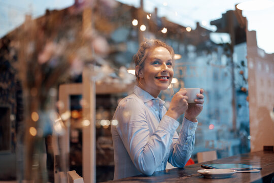 Thoughtful female entrepreneur with coffee cup smiling while looking through cafe window