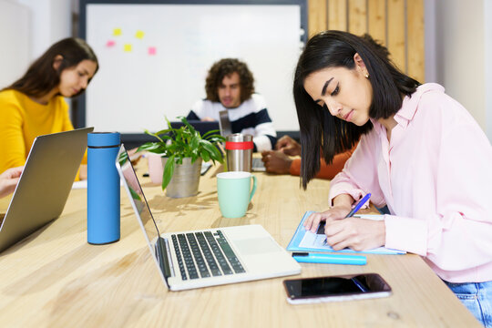 Female creative professional writing at table in office