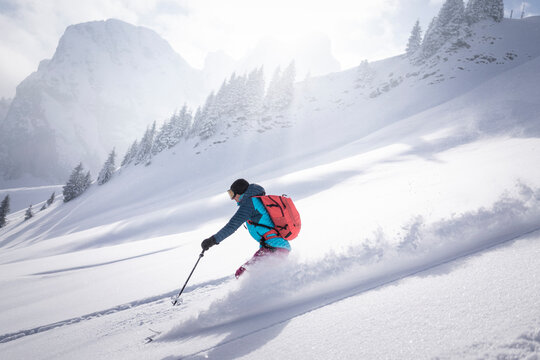 Mid adult woman skiing on snowcapped mountain during sunny day