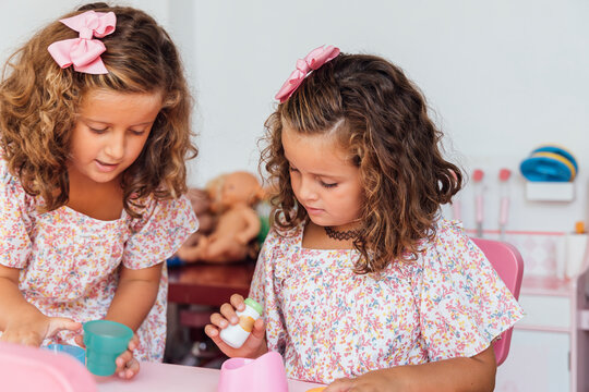 Twin sisters playing with toys at home