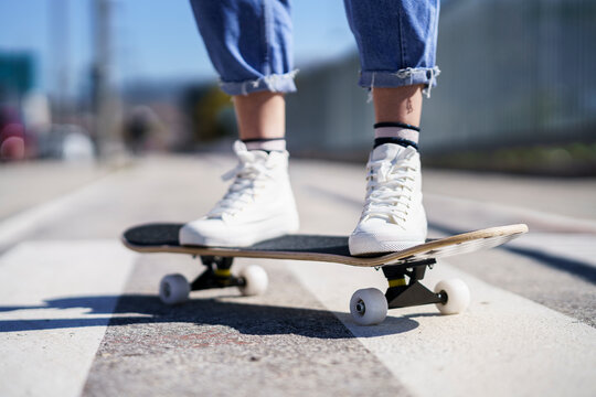 Woman standing on skateboard during sunny day
