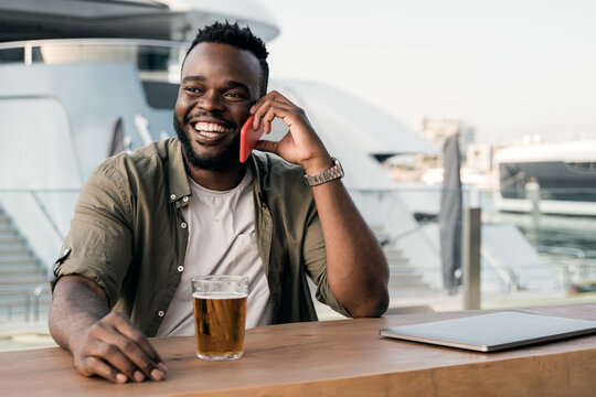 Young african man drinking beer at brewery bar using mobile phone with luxury yacht port in background