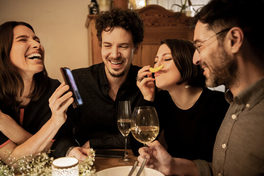 Cheerful woman showing smart phone to male and female friends in birthday celebration at home